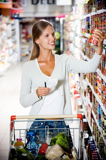 Woman reaching up to get something off of a supermarket shelf : Stock Photo