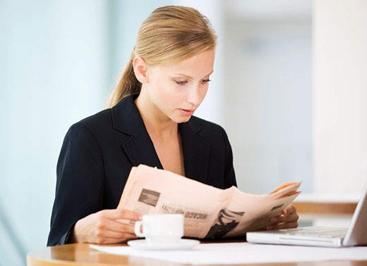 A businesswoman reading a paper : Stock Photo