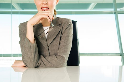 A businesswoman sitting at a table : Stock Photo