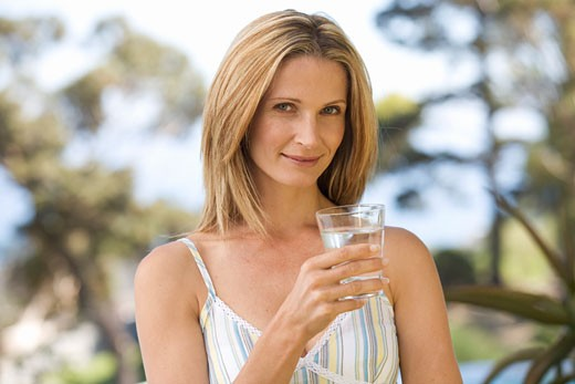 Woman holding a glass of water : Stock Photo