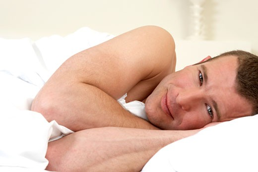 Young man laying in bed : Stock Photo