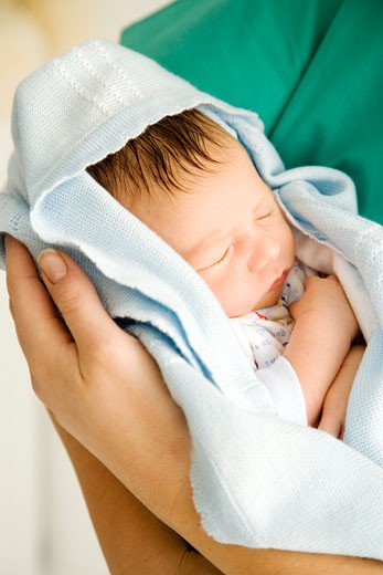 Stock Photo: 1804R-5053 A medical practitioner holding a newborn baby