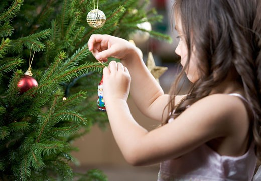 Stock Photo: 1804R-5343 A young girl putting a decoration on a Christmas tree