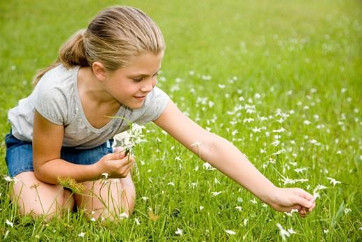 Stock Photo: 1804R-6191 girl sitting on grass picking flowers