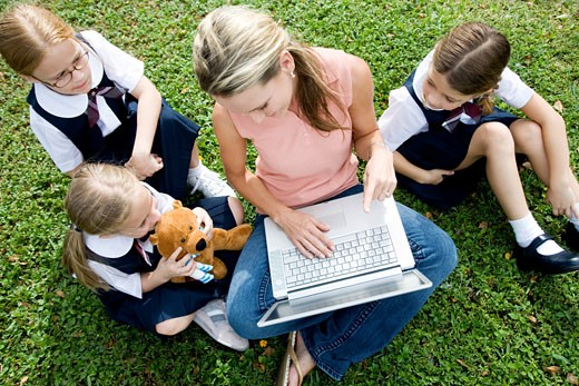 A teacher and children using a laptop outside : Stock Photo