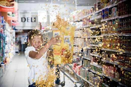 Naughty young girl emptying cereal packet in a supermarket : Stock Photo