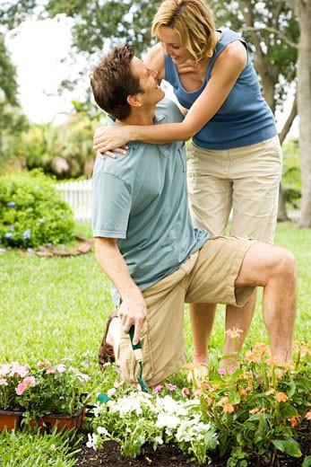 woman embracing gardening husband : Stock Photo