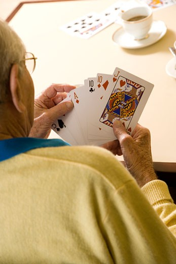 Stock Photo: 1804R-6957 An elderly man playing cards