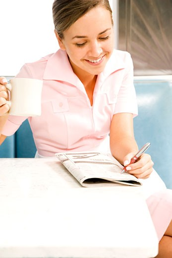 Stock Photo: 1804R-6987 Diner waitress looking at the classified section of a newspaper