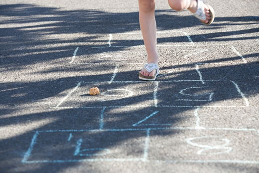 Young girl playing hopscotch : Stock Photo