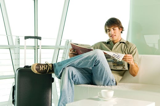 Stock Photo: 1804R-7058 A man with a suitcase waiting in a lobby