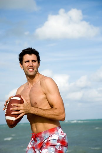 Stock Photo: 1804R-7220 A young man with a ball on the beach