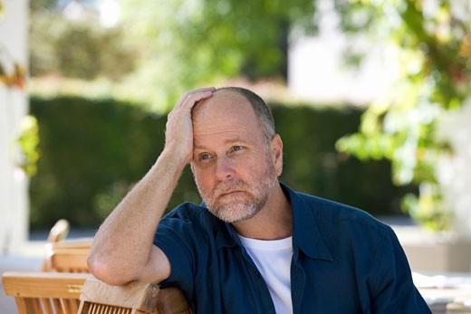 A senior man sitting in a garden : Stock Photo