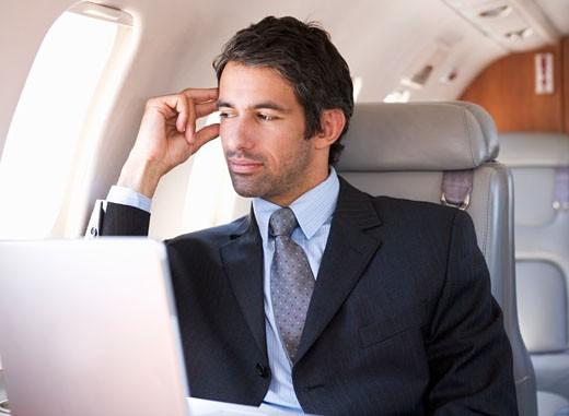 A businessman sitting on a plane : Stock Photo