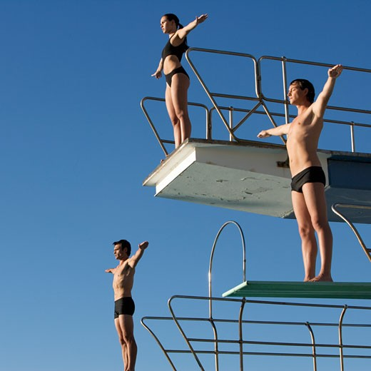 Three divers standing on diving boards : Stock Photo