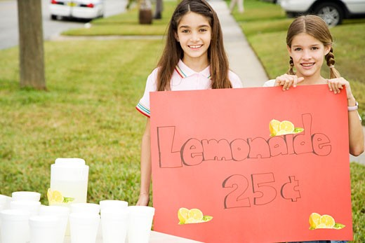 Two young girls at a lemonade stand : Stock Photo