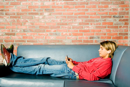 Teenage boy lying on a seat listening to music on mp3 : Stock Photo