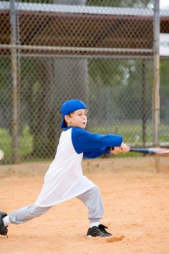 Young boy swinging baseball bat : Stock Photo