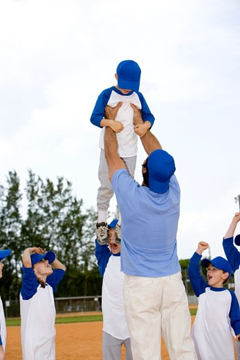 Young boy being lifted up by youth league baseball coach : Stock Photo