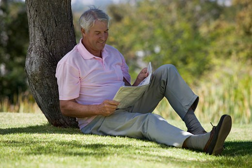 A senior man sitting under a tree reading a newspaper : Stock Photo