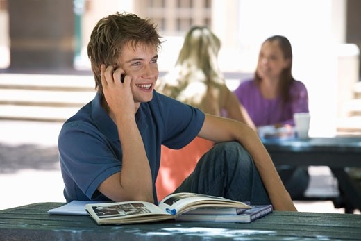 A university student chatting on a mobile phone : Stock Photo