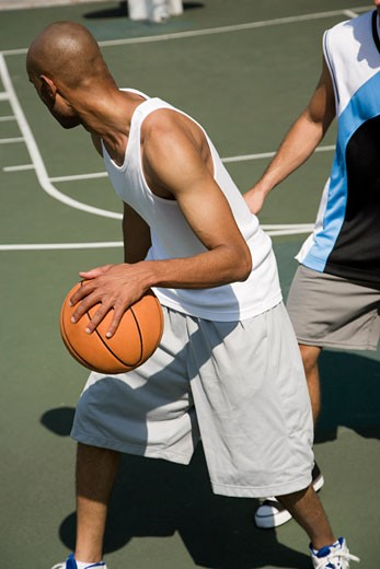 Stock Photo: 1804R-9803 Two men playing basketball on a green urban outside court