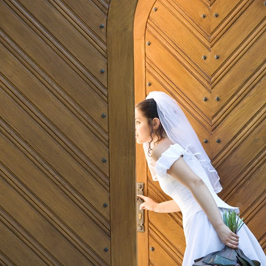 A bride looking through the church doors : Stock Photo