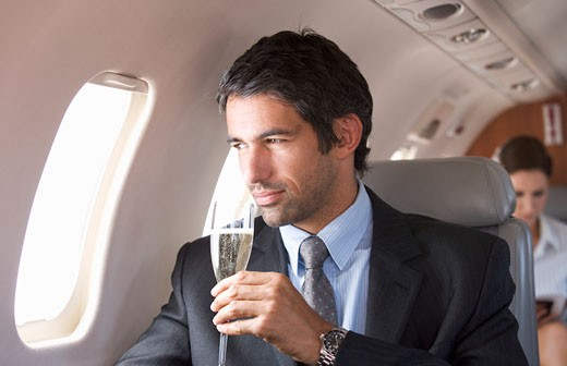 A businessman drinking champagne on a flight : Stock Photo
