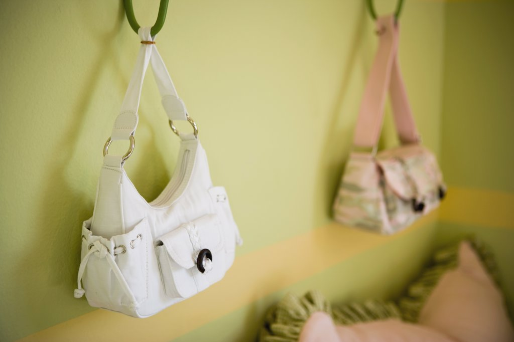 Girl's Purses Hanging on Bedroom Wall : Stock Photo