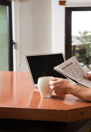 Man Reading Newspaper with Laptop and Coffee : Stock Photo