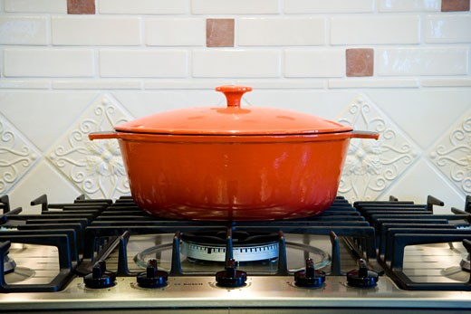 Orange cooking pot on stove top. : Stock Photo