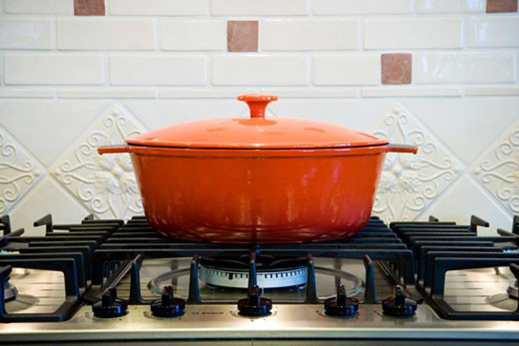 Stock Photo: 1806R-6763 Orange cooking pot on stove top.