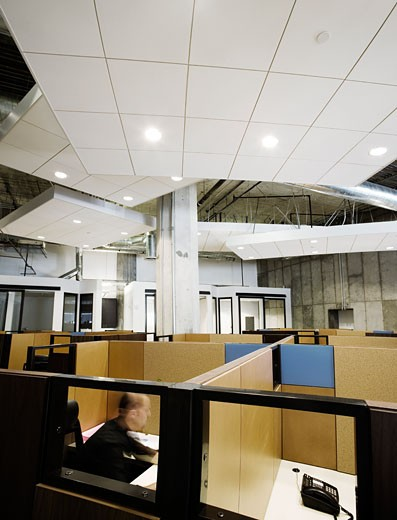Interior of modern office space with cubicles and man working : Stock Photo