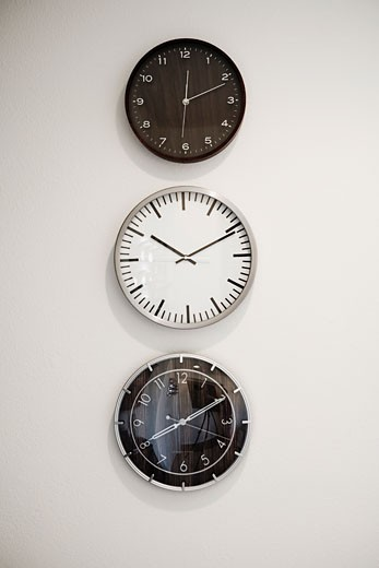 Three clocks on a wall : Stock Photo