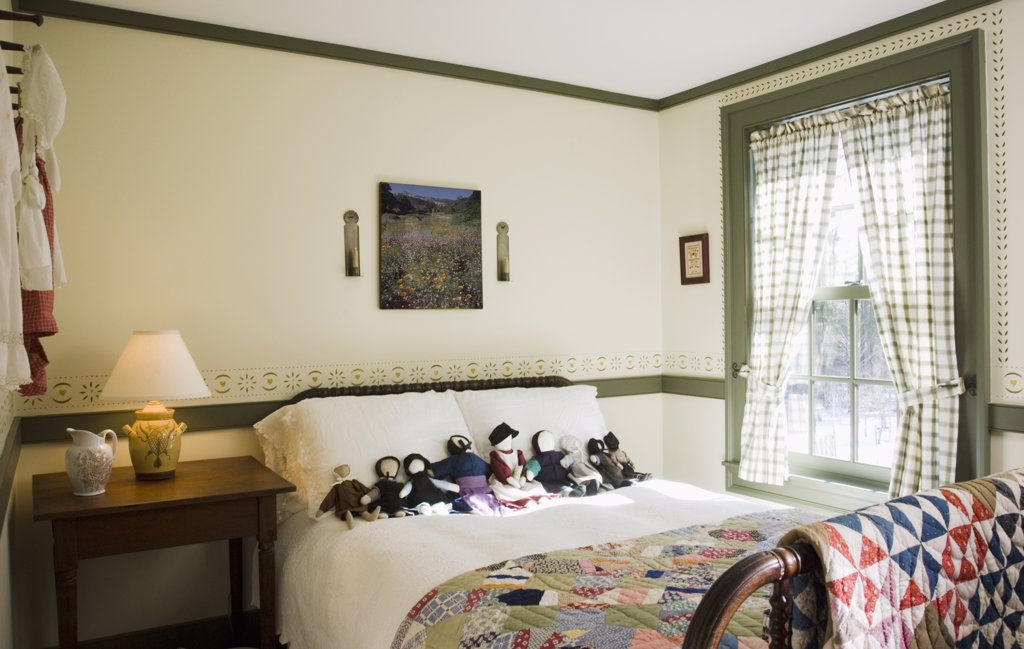 Small colonial bedroom with collection of amish dolls on bed : Stock Photo