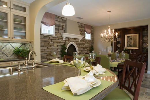 Kitchen with breakfast bar and dining room with stone wall : Stock Photo