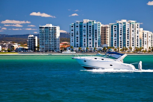 Speedboat in the sea with buildings in the background : Stock Photo