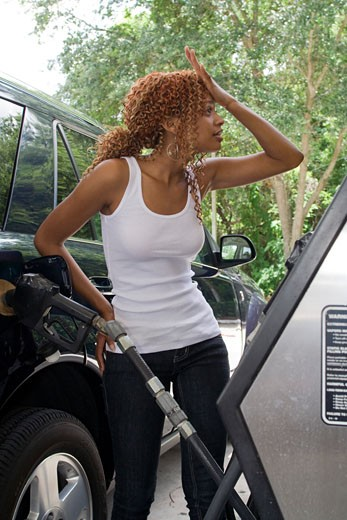 Stock Photo: 1808-103B Young woman holding a fuel pump and shouting at a petrol station