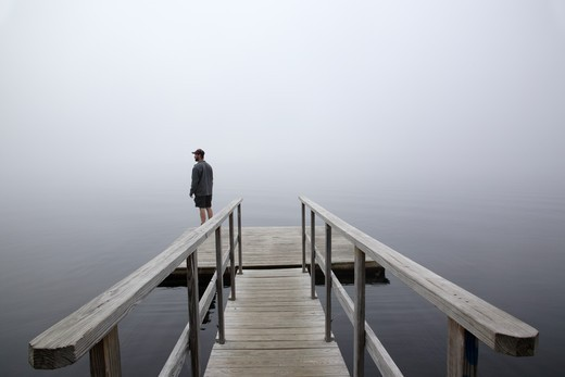 Stock Photo: 1809-10117 A man stands on the edge of a dock overlooking the Connecticut River in foggy conditions...Located in Waterford, Vermont  USA which is part of New England