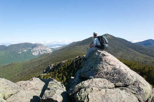 A hiker takes in the views of Franconia Notch from the summit of Mount Liberty during the summer months. Located in the White Mountains, New Hampshire USA : Stock Photo