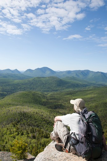 Stock Photo: 1809-12664 Zealand Notch  - A hiker takes in the views from the summit of Zeacliff during the summer months. Located along the Appalachian Trail in the White Mountains, New Hampshire USA