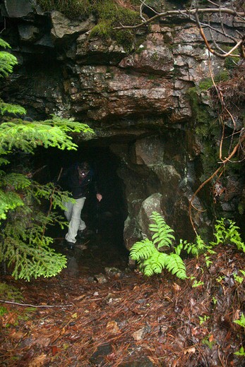 Stock Photo: 1809-12727 A hiker exits a old mine tunnel located on Iron Mountain during the summer months. Located in the White Mountains, New Hampshire USA. This tunnel is about 50 feet long.