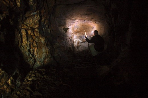 Stock Photo: 1809-12732 A hiker explores a old mine tunnel located on Iron Mountain during the summer months. Located in the White Mountains, New Hampshire USA. This tunnel is about 50 feet long.