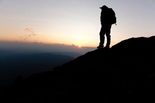 Stock Photo: 1809-13506 A hiker on the Appalachian Trail at sunset near Mount Clay. Located in the White Mountains, New Hampshire USA