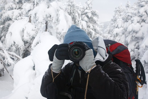 Stock Photo: 1809-14054 A hiker photographing along the Carter Dome Trail in winter conditions near the summit of Carter Dome in the White Mountains, New Hampshire USA