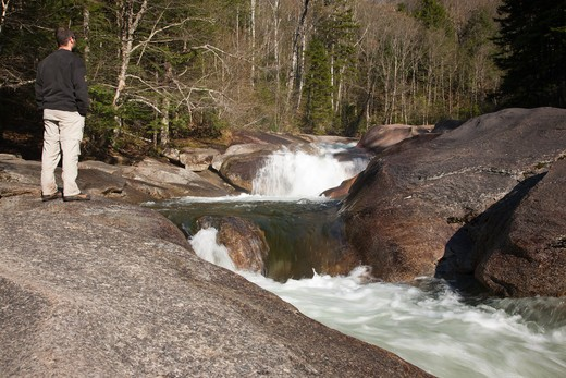 Stock Photo: 1809-15423 A hiker takes in the views of Franconia Falls during the spring months which is located on Franconia Brook in Lincoln, New Hampshire USA