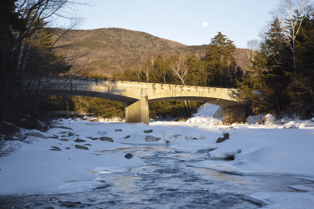 Road Bridge during the in winter months. This bridge crosses the East Branch of the Pemigewasset River in Lincoln, New Hampshire USA along Kancamagus Scenic Byway (Route 112). A suspension bridge used for foot traffic is in the background and a nearly ful : Stock Photo