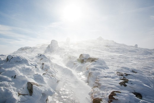 Strong winds blow snow across the summit of Mount Lafayette during the winter months in the White Mountains, New Hampshire USA : Stock Photo