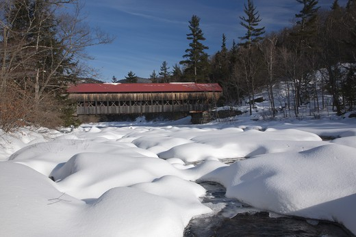 Stock Photo: 1809-6946 Albany Covered Bridge which crosses the Swift River in Albany, New Hampshire, USA just off the Kancamagus Highway. This is the area of 'Blueberry Crossing' along the old Swift River Logging Railroad, which was a logging railroad that operated from 1906 - 1916