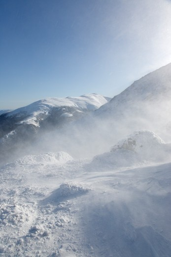 Stock Photo: 1809-8089 Strong winds cause snow to blow off the Mount John Quincy Adams in the Presidential Range during the winter months in the White Mountains, New Hampshire USA. Mount Washington can bee seen in the background